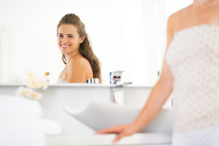 Happy young woman looking in mirror in bathroom Stock Photo - 29382393