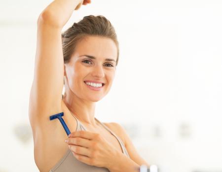 axilla: Portrait of happy young woman shaving armpit Stock Photo