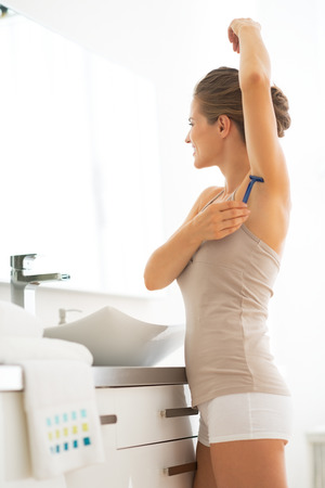 axilla: Young woman shaving armpit in bathroom Stock Photo
