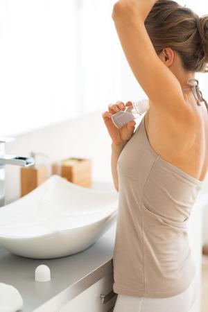 axilla: Young woman applying deodorant on underarm Stock Photo