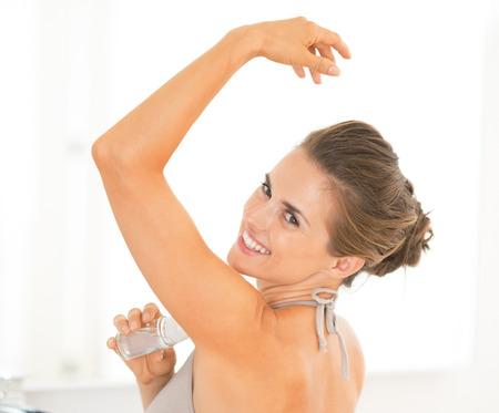 underarm: Portrait of happy young woman applying deodorant on underarm Stock Photo