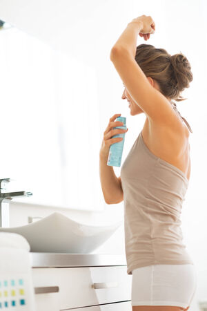 Young woman applying deodorant on underarm Stock Photo