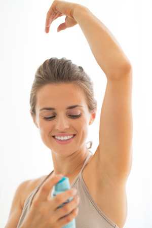 underarm: Happy young woman applying deodorant on underarm