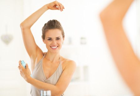 beautiful armpit: Happy young woman applying deodorant on underarm