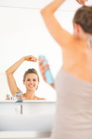 axilla: Happy young woman applying deodorant on underarm in bathroom