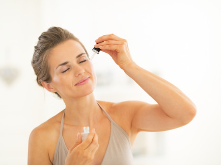 moisten: Portrait of young woman applying cosmetic elixir in bathroom Stock Photo
