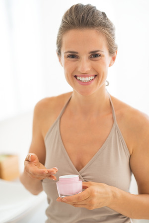 Portrait of happy young woman with cream in bathroom Stock Photo - 29004532