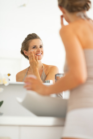 Happy young woman applying cream in bathroom Stock Photo - 29004540