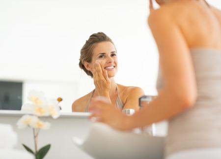Happy young woman applying cream in bathroom Stock Photo - 29004541