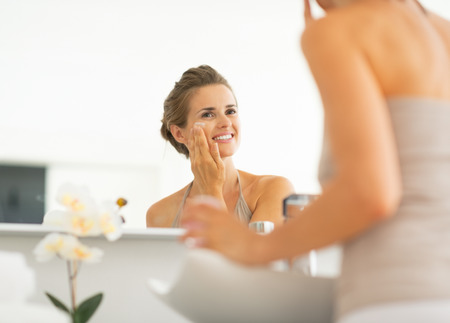 Happy young woman applying cream in bathroom Stock Photo - 29004541