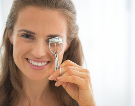 Portrait of happy young woman using eyelash curler Stock Photo - 29305263