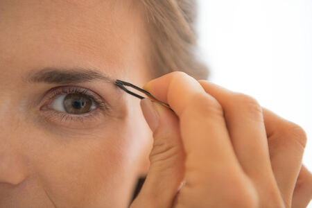 Closeup on young woman tweezing eyebrows Stock Photo - 29305267