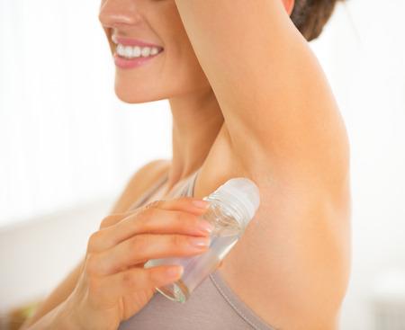 Vértes boldog fiatal nő alkalmazása dezodor a hónaljban