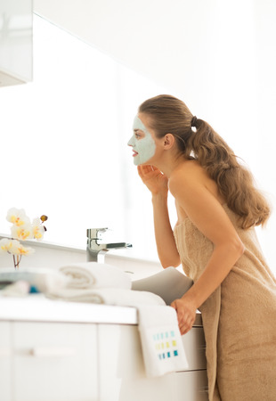 Young woman wearing facial cosmetic mask in bathroom looking in mirror photo