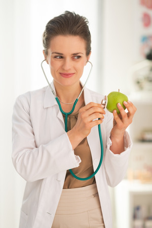 Happy medical doctor woman examining apple with stethoscope photo