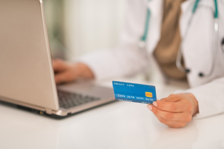 topicality: Closeup on medical doctor woman with credit card using laptop
