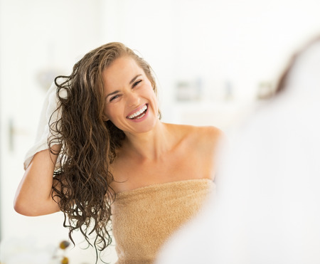 Portrait of smiling young woman wiping hair with towel Фото со стока