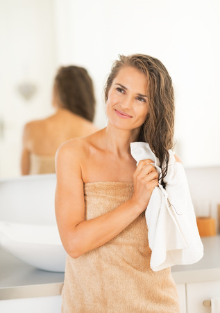 Portrait of happy young woman wiping hair with towel photo