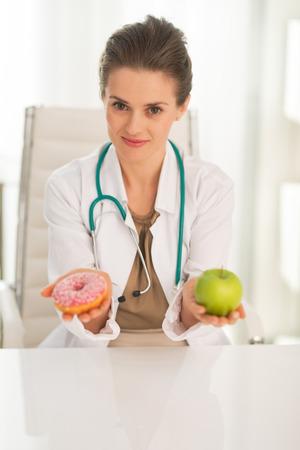 Mujer del médico dando a elegir entre la manzana y donuts Foto de archivo