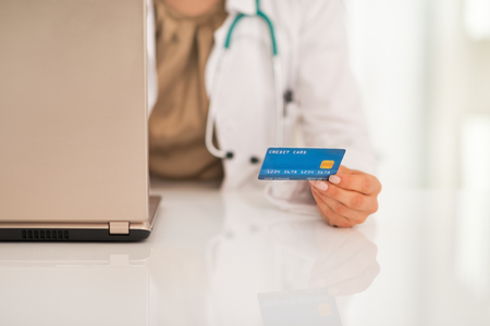 Closeup on medical doctor woman with credit card using laptop Stock Photo - 29043685