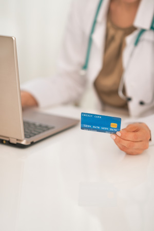 Closeup on medical doctor woman with credit card using laptop Stock Photo - 29090666