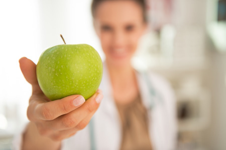 Closeup on happy medical doctor woman giving apple Stock Photo - 29090667