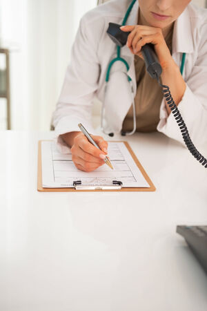 Closeup on medical doctor woman with phone writing in clipboard Stock Photo - 29090668