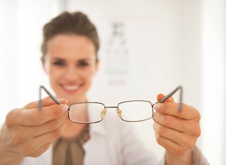 Closeup on ophthalmologist doctor woman giving eyeglasses Stock Photo