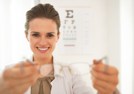 Smiling ophthalmologist doctor woman giving eyeglasses in front of snellen chart Stock Photo - 29090671