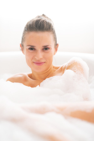 Portrait of happy young woman laying in bathtub photo