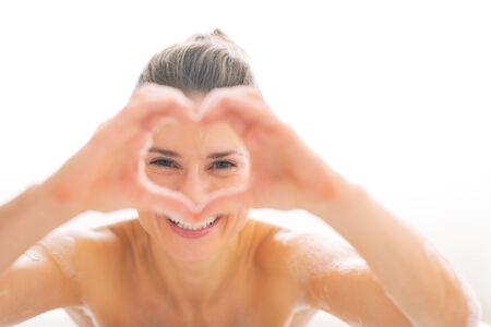 shaped hands: Young woman in bathtub looking through heart shaped hands