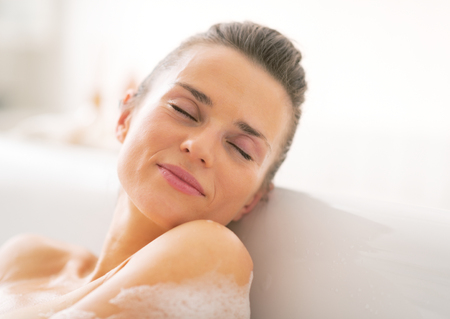 woman bath: Portrait of young woman relaxing in bathtub Stock Photo