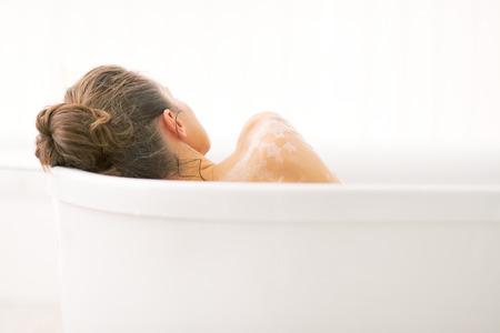 Joven mujer de relax en la bañera. vista trasera Foto de archivo