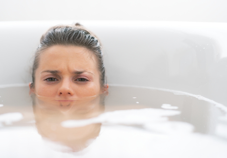 Stressed young woman laying in bathtub Stock Photo