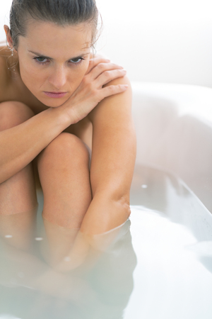 Stressed young woman sitting in bathtub Stock Photo - 29325140