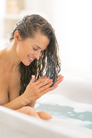 Young woman applying hair conditioner in bathtub Stock Photo - 29325155