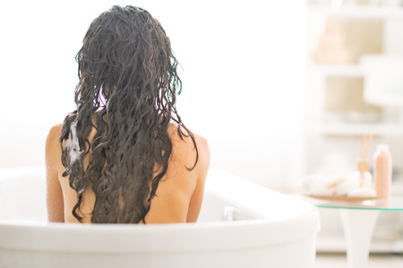 Young woman sitting in bathtub. rear view Stock Photo - 29325158
