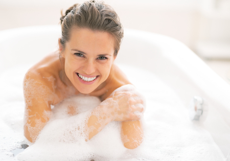 Happy young woman sitting in bathtub Stock Photo - 29325163