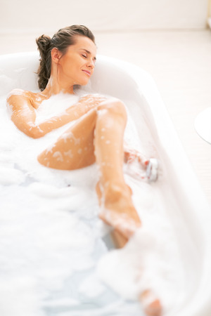 Relaxed young woman laying in bathtub Stock Photo - 29325164
