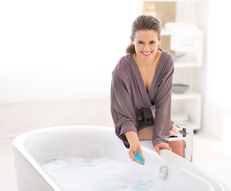 Młoda kobieta, dodając sól do kąpieli w wannie Zdjęcie Seryjne