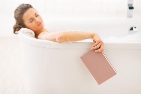 Jonge vrouw in slaap vallen tijdens het lezen van boek in bad