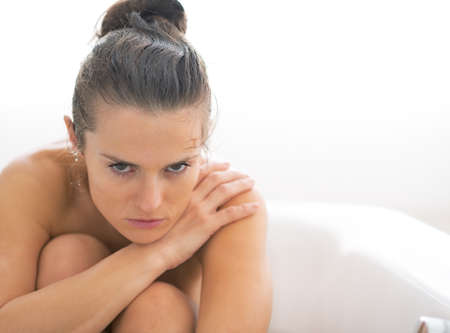 Frustrated young woman sitting in bathtub photo
