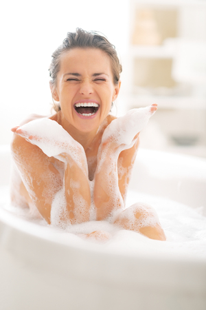 woman bath: Happy young woman playing with foam in bathtub Stock Photo