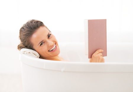 Happy young woman reading book in bathtub Stock Photo - 29338184