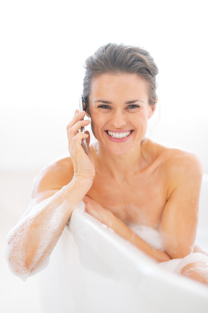 Happy young woman talking mobile phone in bathtub Stock Photo - 29338187