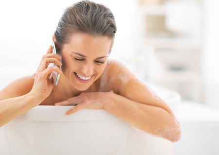 Happy young woman talking cell phone in bathtub Stock Photo - 29338188