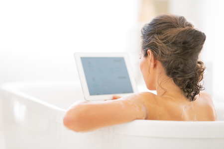 Young woman using tablet pc in bathtub. rear view Stock Photo - 29338189