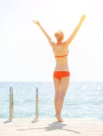 rejoicing: Young woman on bridge rejoicing. rear view