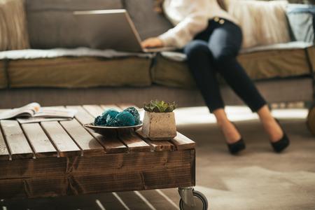 Nahaufnahme auf einem Couchtisch und junge Frau mit Laptop im Hintergrund
