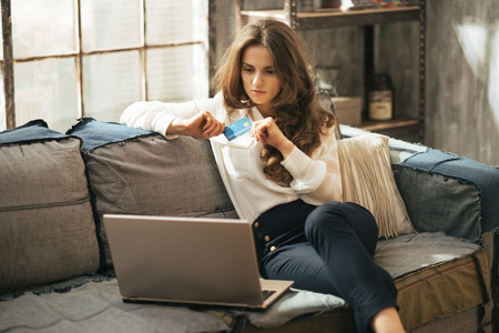 Junge Frau mit Kreditkarte mit Laptop im Loft-Wohnung